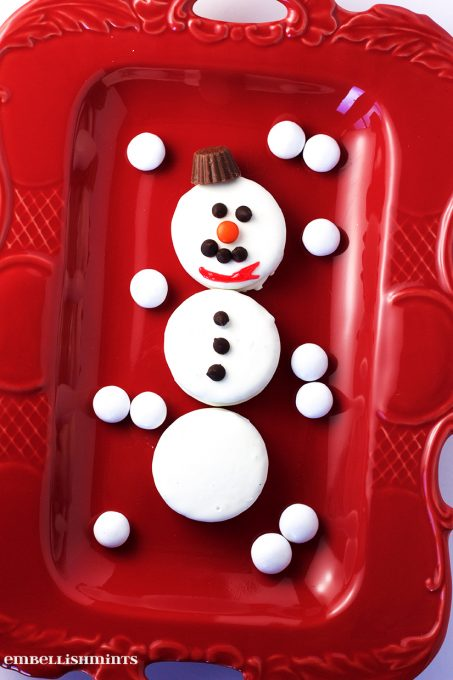 These Oreo Snowman Cookies are festive and will be the first to go at your holiday party. So cute! www.Embellishmints.com