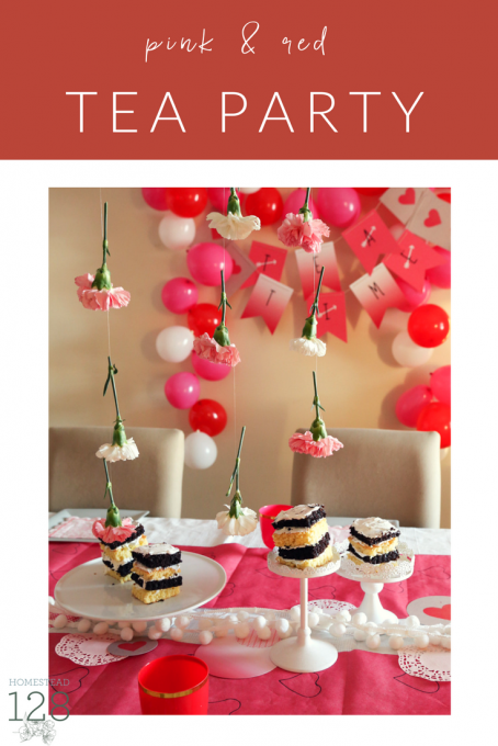 A pink and red colored tea party for little girls with flowers, cake, hearts and balloons.